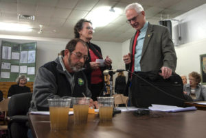 """Sen. Ken Haar speaks with a local activist at the March 24 NOGCC hearing, where another citizen poured the glasses of """"fracked water"""" on the table for Commissioners (as seen in this video viewed 1.8 million times on YouTube). Photo: Mark Hefflinger"""