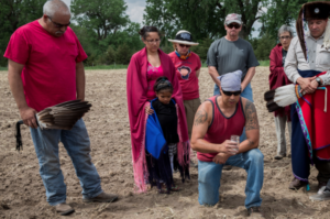 """Mekasi Horinek  (kneeling) prays over water during the first planting of sacred Ponca corn """"Seeds of Resistance"""" on the Tanderup farm in Neligh, Nebraska, May 2014 (Photo: Mary Anne Andrei)"""