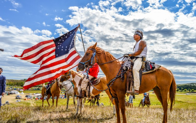 Water defenders on horseback carrying a replica battle flag of the one taken from General Custer. 8 Sept 2016. Rob Wilson for Bold Alliance.